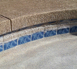 Calcium hardness staining along the tile of a swimming pool